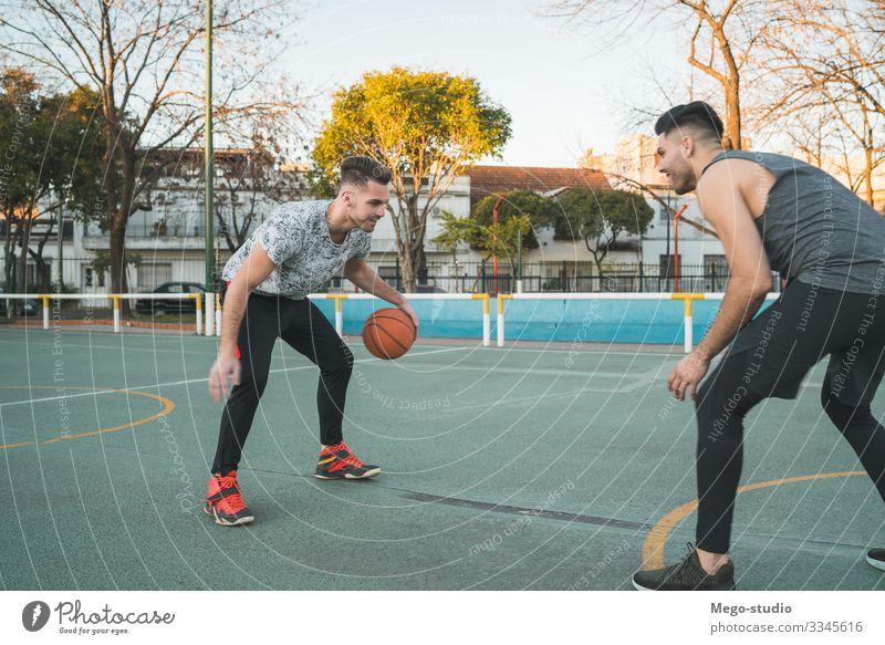 Zwei junge Freunde spielen Basketball. Lifestyle Freude Glück Erholung Freizeit & Hobby Spielen Sport Ball Mensch maskulin Junge Mann Erwachsene Freundschaft 2