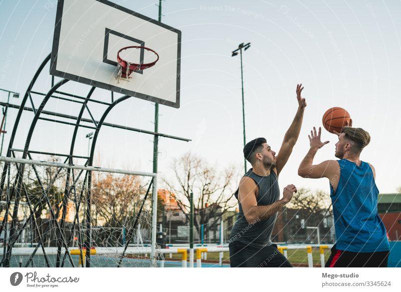 Junge Basketballspieler im Einzelspiel. Freude Glück Erholung Freizeit & Hobby Spielen Sport Ball Mensch maskulin Mann Erwachsene Freundschaft 2 Menschengruppe
