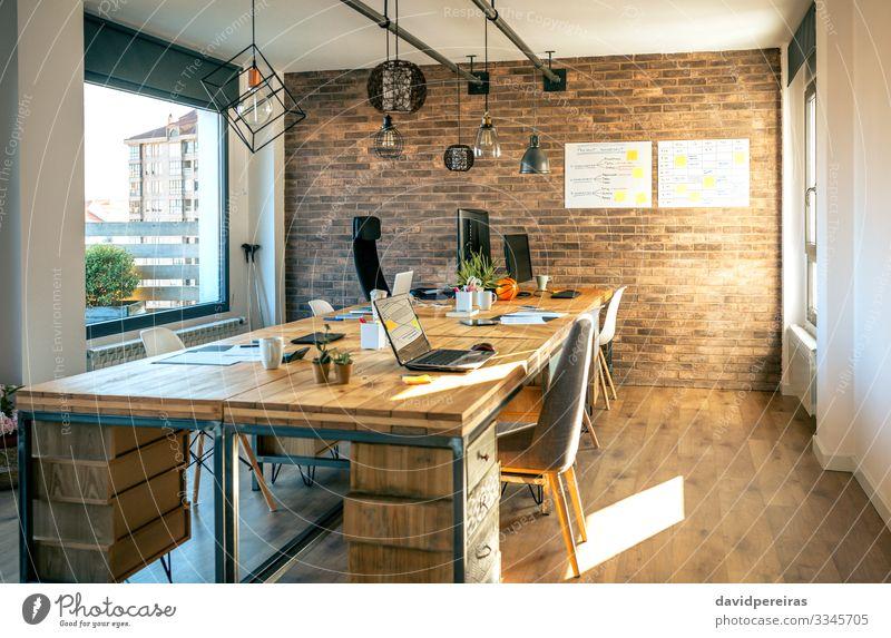 Interieur eines Coworking-Büros im Industriestil Design Dekoration & Verzierung Lampe Schreibtisch Stuhl Tisch Arbeitsplatz Business Computer Notebook Pflanze