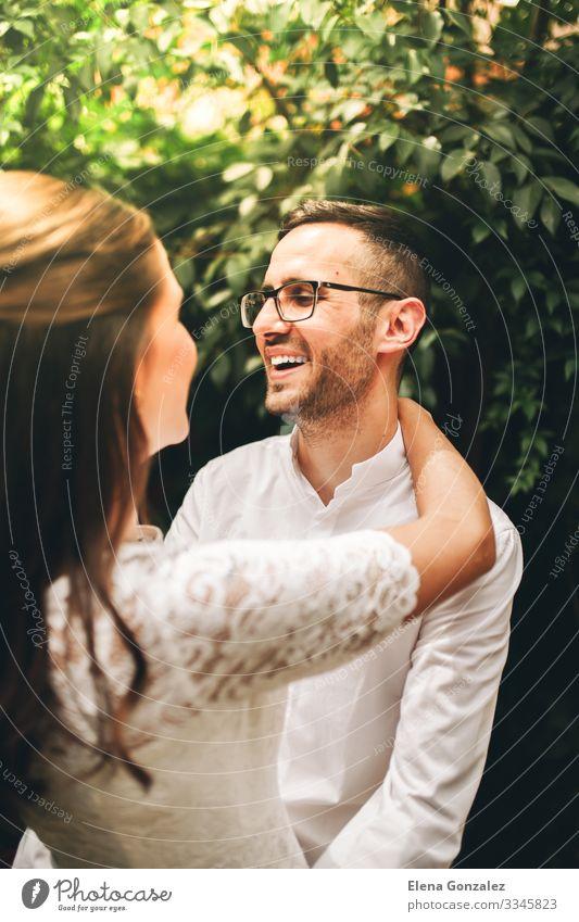 Frisch verheiratetes Paar, das sich gegenseitig anschaut und lächelt. Garten Feste & Feiern Hochzeit Frau Erwachsene Mann Küssen Liebe Umarmen Gefühle Romantik