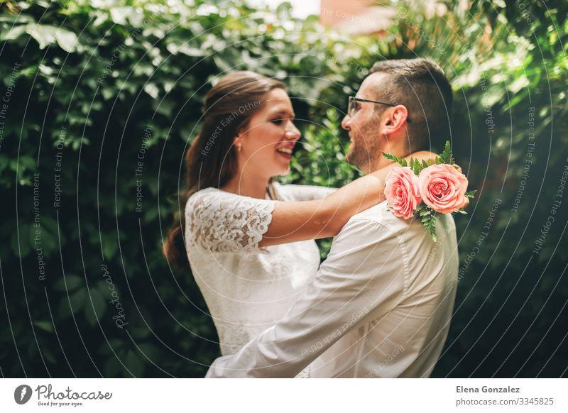 Frisch verheiratetes Paar, das sich gegenseitig umarmt und tanzt. Garten Feste & Feiern Hochzeit Frau Erwachsene Mann Rose Blumenstrauß Küssen Liebe Umarmen