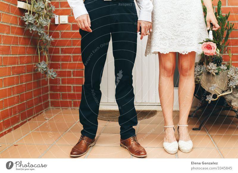 Die Schuhe des Bräutigams und der Braut und ihr kleiner Hochzeitsstrauß. Feste & Feiern feminin Frau Erwachsene Hand Rose Blumenstrauß Liebe Zusammensein