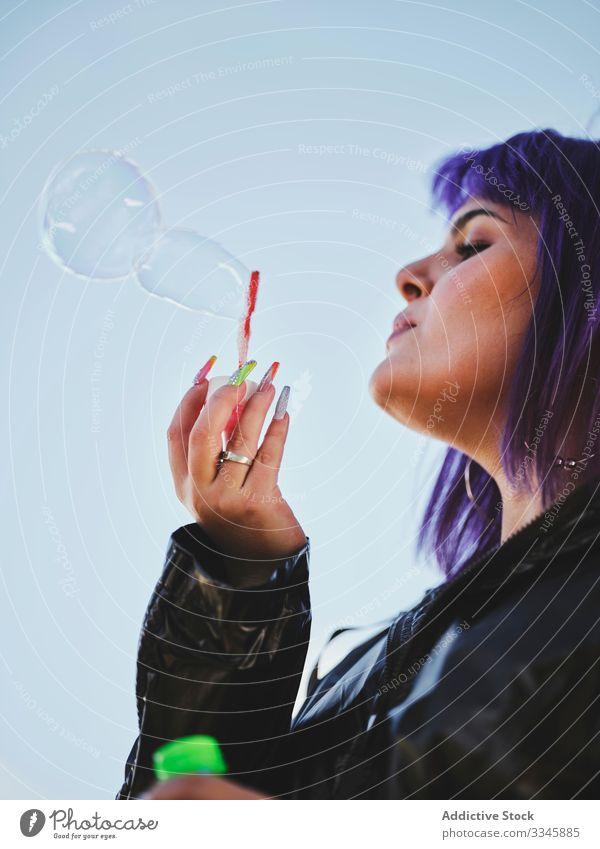 Frau bläst Seifenblasen am hellen Tag blasend Schaumblase purpur stylisch lustig niedlich heiter Lachen lieblich Frisur Spielen Freude Spaß haben Gesundheit