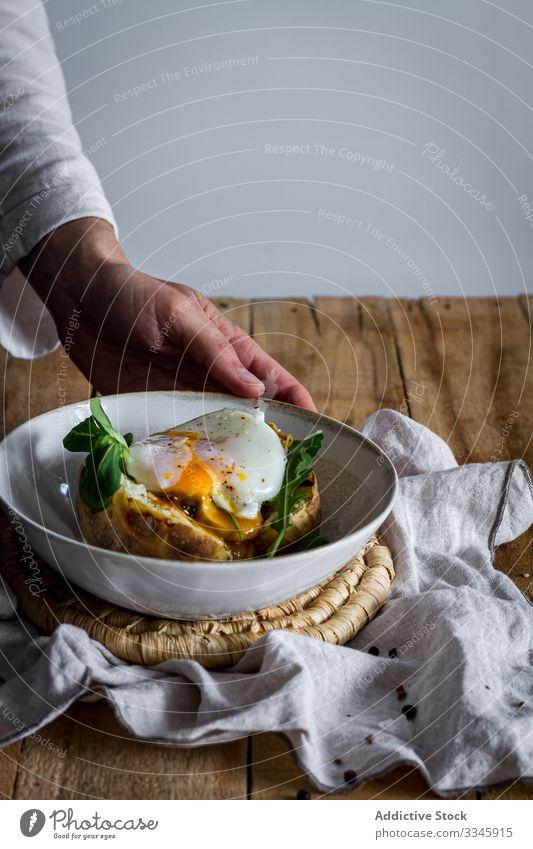 Tisch mit Zutaten zum Kochen und offener Kartoffel mit Ei Lebensmittel Essen zubereiten Prozess hölzern gebraten Kraut Käse Gewürz Erdöl Hand Messer Schneiden