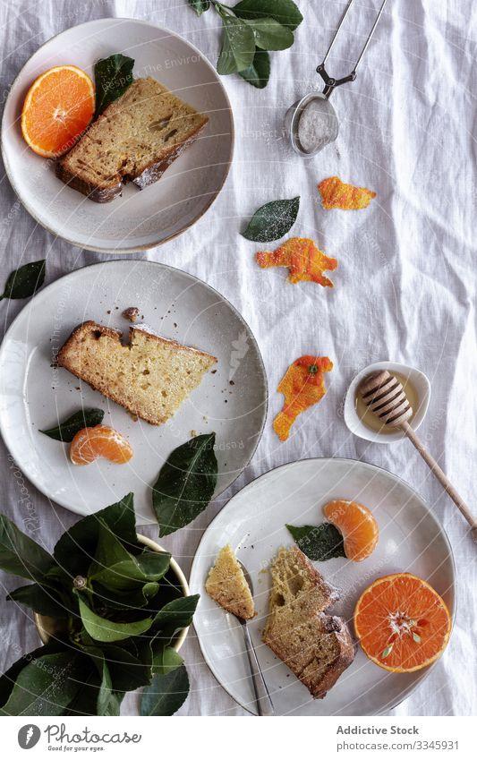 Geschnittener Kuchen und Zitrusfrüchte auf Tellern auf dem Tisch Mandarine Frucht Dessert aufgeschnitten Portion Essen orange süß Gebäck Feinschmecker lecker