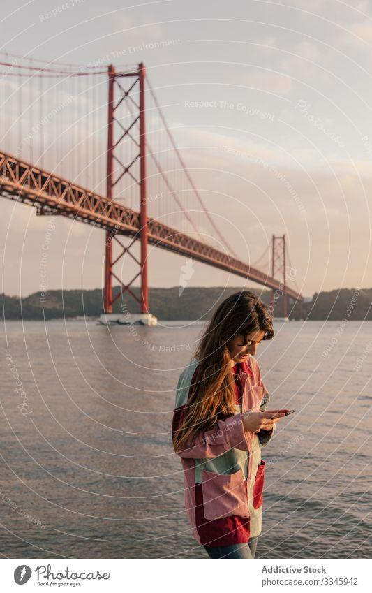 Glückliche Frau surft mit Smartphone gegen Brücke benutzend Handy Nachrichtenübermittlung Freizeit sich[Akk] entspannen Lissabon Portugal Mitteilung Anschluss
