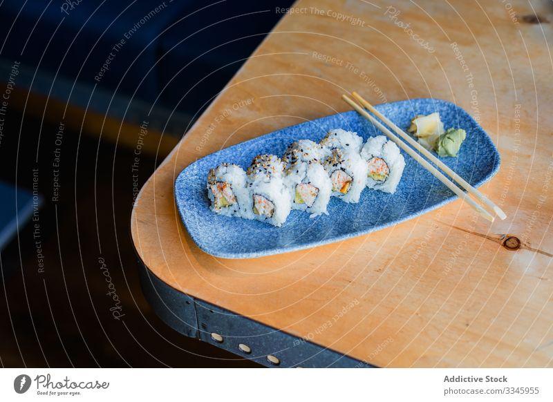 Frisches Sushi mit Stäbchen auf dem Tisch Asiatische Küche Speise Essstäbchen Reis hölzern Ingwer Wasabi Sesam Abendessen traditionell Meeresfrüchte Teller