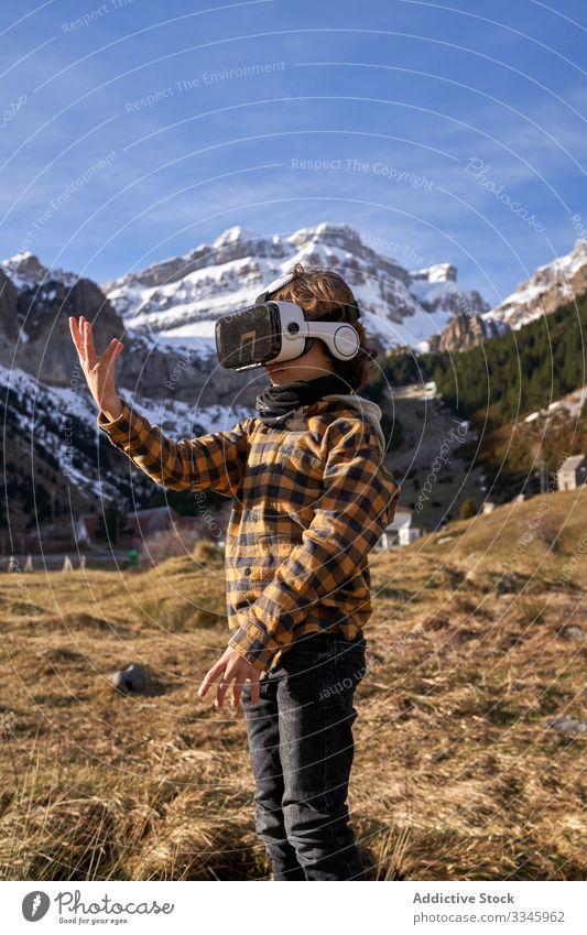 Auf Stein stehender Junge mit VR-Brille gegen Berg Natur Tal Berge u. Gebirge virtuell Realität Headset modern Gerät Entertainment erkunden Gelände
