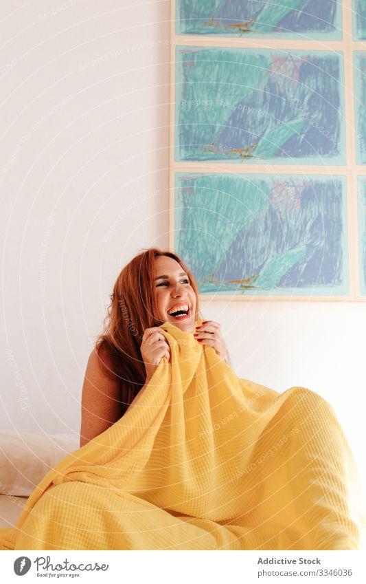 Junge rothaarige Frau liegt an einem sonnigen Morgen im Bett Sitzen Deckung Decke gelb sich[Akk] entspannen ruhen Lächeln genießen spielerisch Rotschopf
