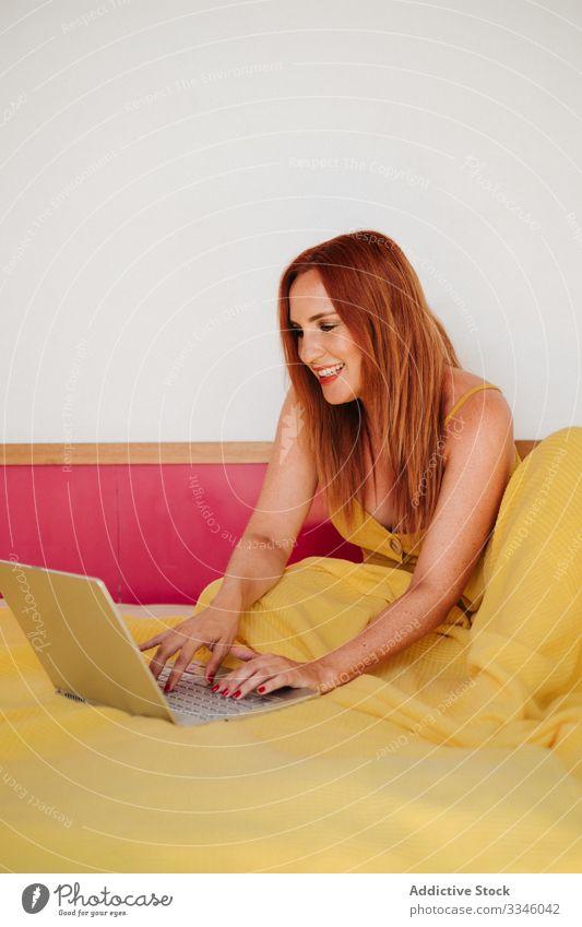 Frau, die zu Hause am Laptop im Bett arbeitet heimwärts benutzend Browsen freiberuflich Lügen Morgen beschäftigt klug gelb Kleid Lifestyle jung Internet Sitzen