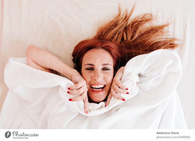 Positive Dame versteckt sich zu Hause unter einer Decke Frau Lügen Bett versteckend Morgen Sitzen Deckung Spaß unten sich[Akk] entspannen ruhen Lächeln genießen