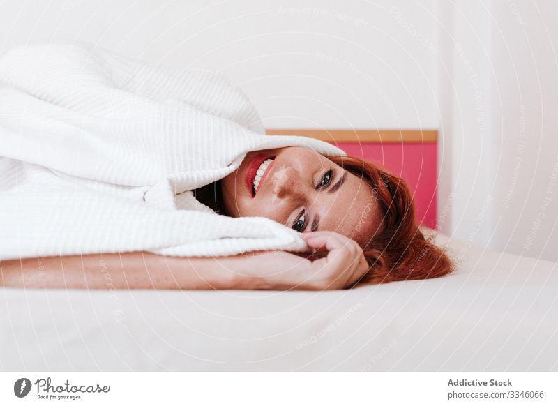Positive Dame zu Hause in der Wette liegend Frau Lügen Bett versteckend Decke Morgen Sitzen Deckung Spaß unten sich[Akk] entspannen ruhen Lächeln genießen