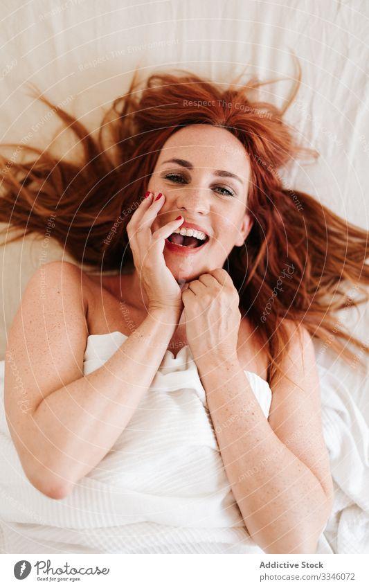 Positive Dame versteckt sich zu Hause unter einer Decke Frau Lügen Bett versteckend Morgen Sitzen Deckung gelb Spaß unten sich[Akk] entspannen ruhen Lächeln