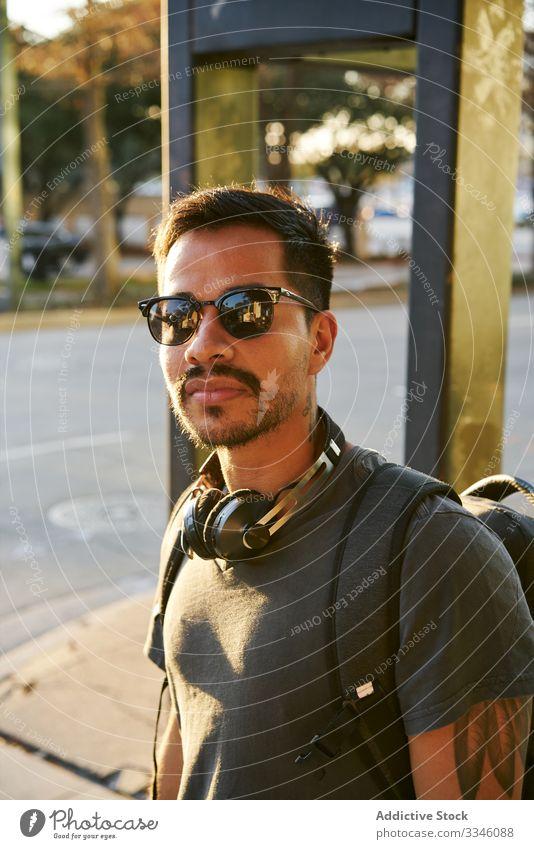 Zeitgenössischer Hispanoamerikaner auf der Straße in der Stadt Mann laufen Großstadt Sonnenuntergang Sonnenbrille lässig Kopfhörer Zubehör Rucksack Hipster