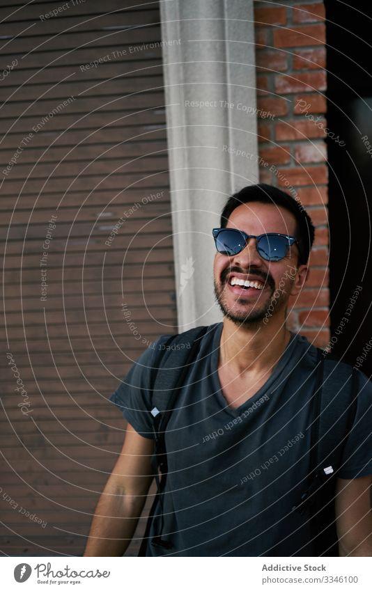 Junger spanischer Mann mit Rucksack auf dem Bürgersteig Straße Großstadt lässig männlich jung Backsteinwand Gebäude ethnisch hispanisch lateinamerikanisch