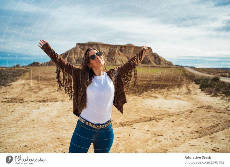 Fröhliche Touristin genießt Reise in der Wüste Frau genießen reisen Urlaub Lächeln erhobene Hände lässig stylisch Sonnenbrille Sommer wüst Ausflug Tourismus