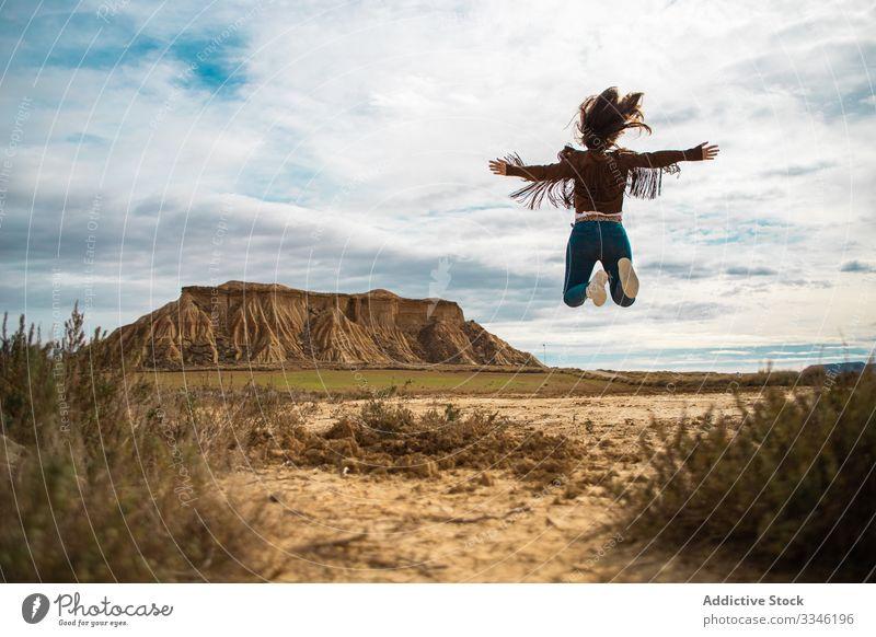 Überglückliche anonyme Reisende beim Sprung in die Wüste Frau genießen reisen springen Urlaub Lächeln erhobene Hände lässig stylisch Sonnenbrille Bewegung