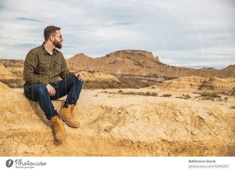 Junger Mann sitzt im Urlaub in der Nähe einer Klippe in der Wüste Tourismus Berge u. Gebirge wüst Felsen Stein lässig Sitzen Sonnenbrille stylisch Blauer Himmel