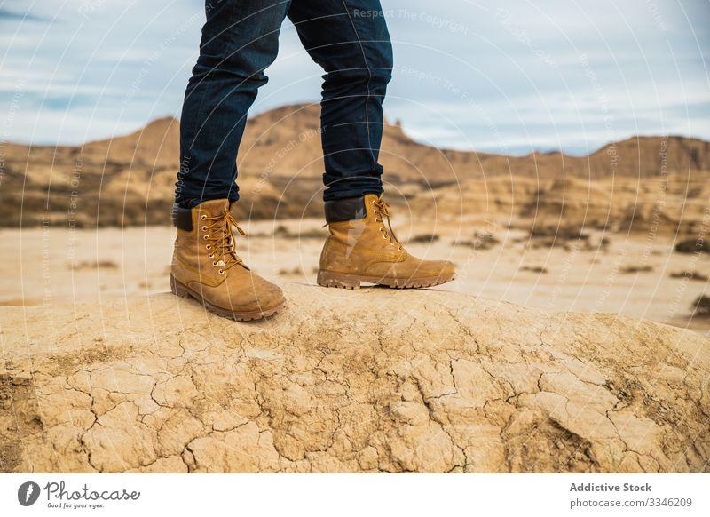 Anonymer Tourist zwischen Wüste mit Klippen Reisender Tourismus wüst Beine Stiefel Berge u. Gebirge Jeanshose lässig Hügel Himmel wandern Trekking Abenteuer