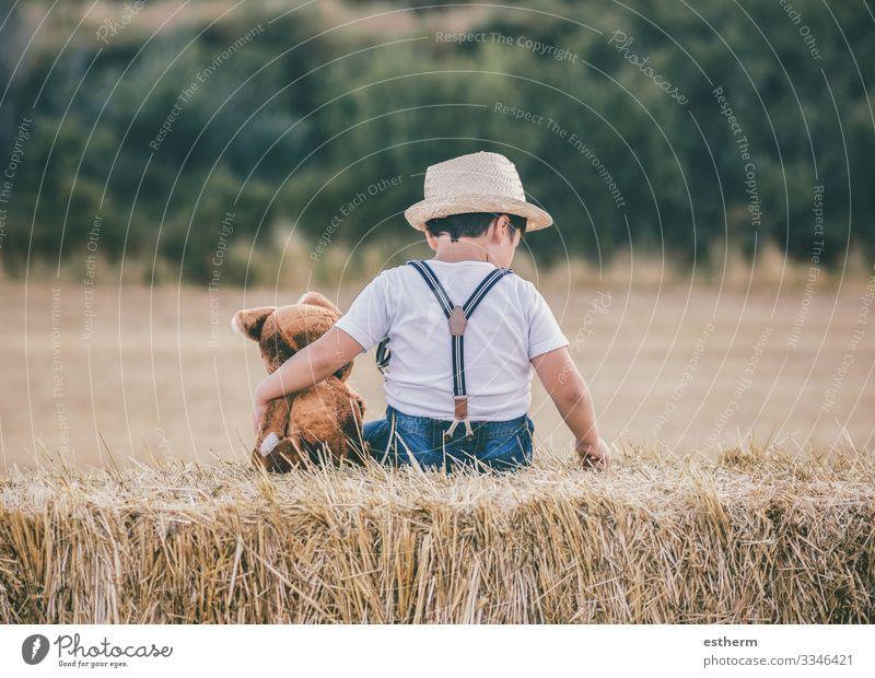 Junge umarmt Teddybär im Weizenfeld im Freien Freude Spielen Ferien & Urlaub & Reisen Freiheit Sommer Mensch maskulin Kind Kleinkind Familie & Verwandtschaft