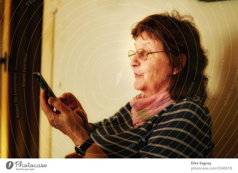 Geübter Blick ins Handy Mensch feminin Frau Erwachsene Weiblicher Senior Freundschaft 1 60 und älter entdecken lesen lernen Telefongespräch natürlich blau