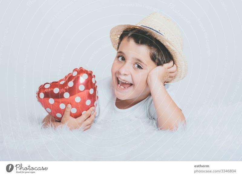 Lächelndes Kind mit einem herzförmigen Luftballon auf weißem Hintergrund Lifestyle Freude Gesundheitswesen Medikament Feste & Feiern Valentinstag Muttertag