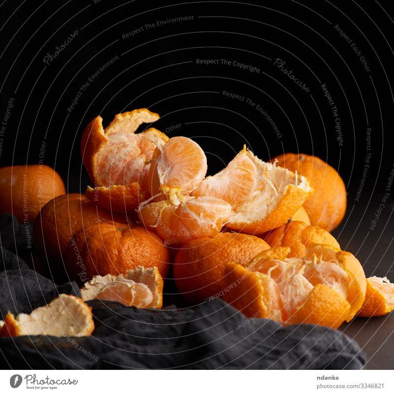 Haufen ungeschälter runder reifer orangefarbener Mandarinen Frucht Dessert Ernährung Vegetarische Ernährung Saft Teller Tisch Holz dunkel frisch natürlich