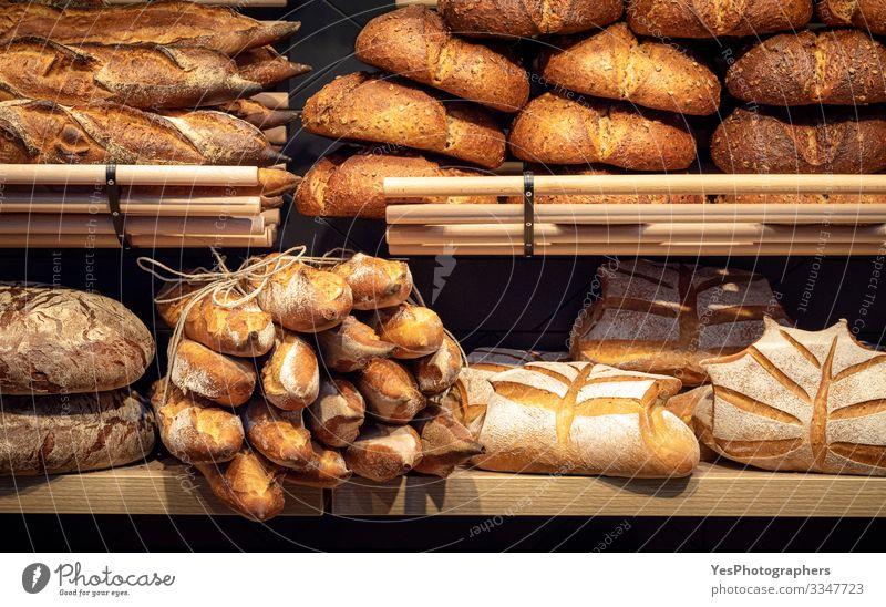 Brotsortiment in Holzregalen der Bäckerei. Brotgeschäft Lebensmittel Teigwaren Backwaren Brötchen Ernährung kaufen Gesunde Ernährung Tradition Baguette