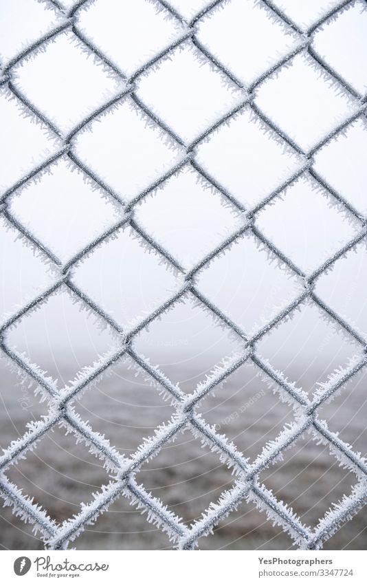 Eingefrorener Metallzaun. Mit Schnee bedeckter Drahtzaun Winter schlechtes Wetter Nebel Eis Frost Stahl frieren kalt weiß Schutz Geborgenheit Hintergrund