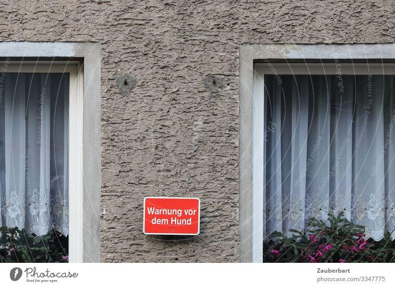 Warnung vor dem Hund Topfpflanze Einfamilienhaus Fenster Gardine Fensterrahmen Tüll Stein Schriftzeichen Hinweisschild Warnschild trist grau rot weiß Angst