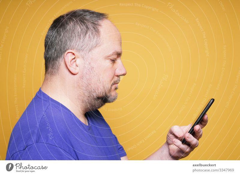 Mann schaut auf Smartphone Lifestyle Freizeit & Hobby Telefon Handy PDA Technik & Technologie Unterhaltungselektronik Telekommunikation Informationstechnologie