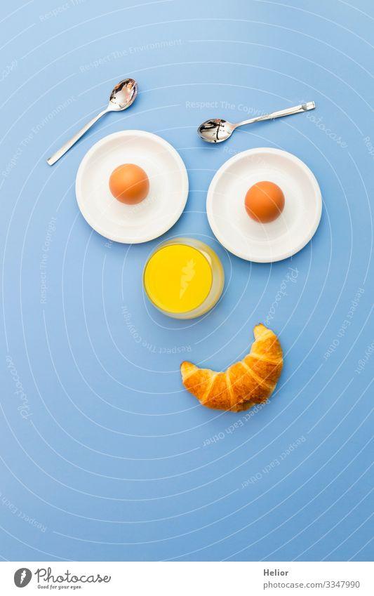 Lustiges Frühstückskonzept mit abstraktem menschlichem Gesicht Croissant Getränk Saft Teller Löffel Freude Erholung Essen androgyn Lächeln Blick Freundlichkeit