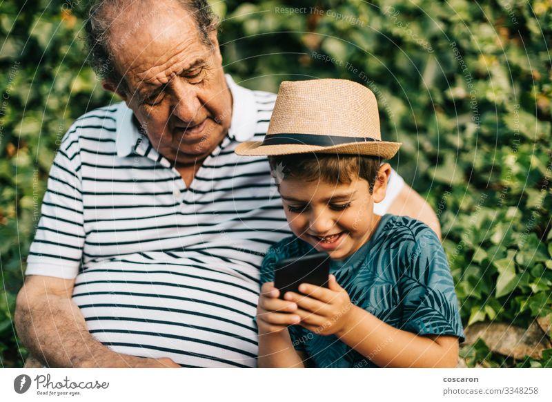 Großvater und Enkel spielen mit einem Mobiltelefon Lifestyle Glück Freizeit & Hobby Spielen Ferien & Urlaub & Reisen Tourismus Sommer Sommerurlaub Kind