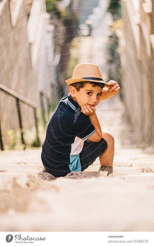 Porträt eines süßen Jungen mit Hut auf einer Treppe Lifestyle Stil Freude Glück schön Sommer Sommerurlaub Sonne Kind Fotokamera Mensch Kleinkind Kindheit 1