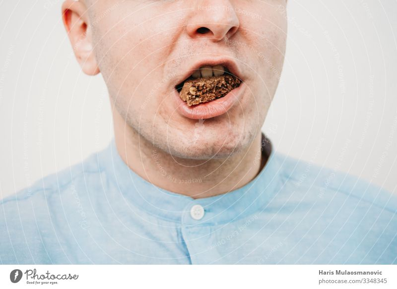 Mann isst Schokolade aus nächster Nähe Lebensmittel Essen Diät füttern Bonbon Keks Kalorie Mund Farbfoto Innenaufnahme Studioaufnahme Textfreiraum links