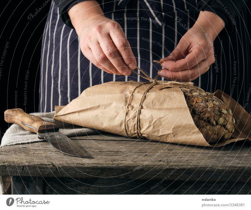 ganzer gebackener Laib Brot Brötchen Ernährung Essen Tisch Küche Seil Frau Erwachsene Hand Papier Holz machen dunkel frisch lecker braun schwarz Tradition