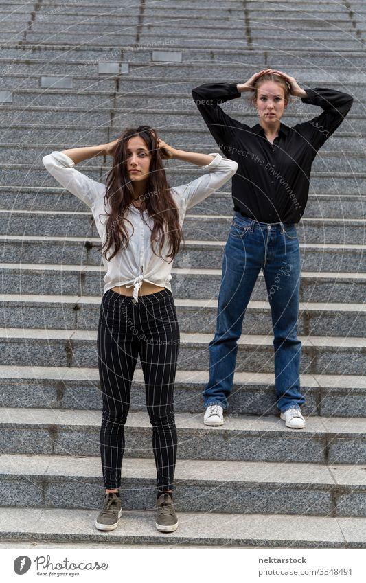 Zwei Frauen posieren auf Schritten mit Händen in den Haaren Erwachsene Jugendliche Jugendkultur Zufriedenheit Tanzen Mädchen Freitreppe Hände im Haar