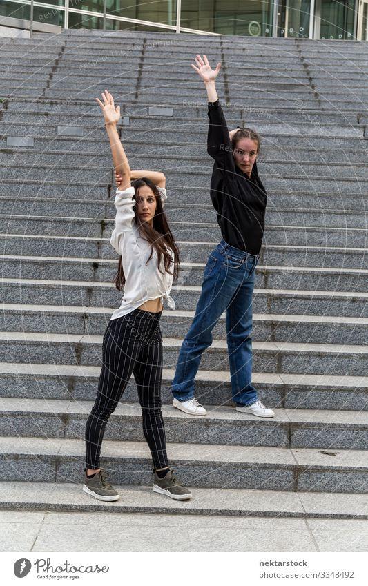 Zwei Frauen posieren auf Stufen mit erhobenen Armen Erwachsene Jugendliche Jugendkultur Zufriedenheit Tanzen Mädchen Freitreppe Arme hochgezogen Treppenhaus