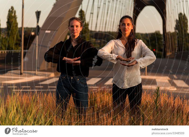 Zwei Frauen in Tanzposen auf Straßenrandgras Erfolg Erwachsene Jugendliche Gras Zufriedenheit Tanzen Mädchen Pose Handzeichen gestikulieren Tänzerinnen