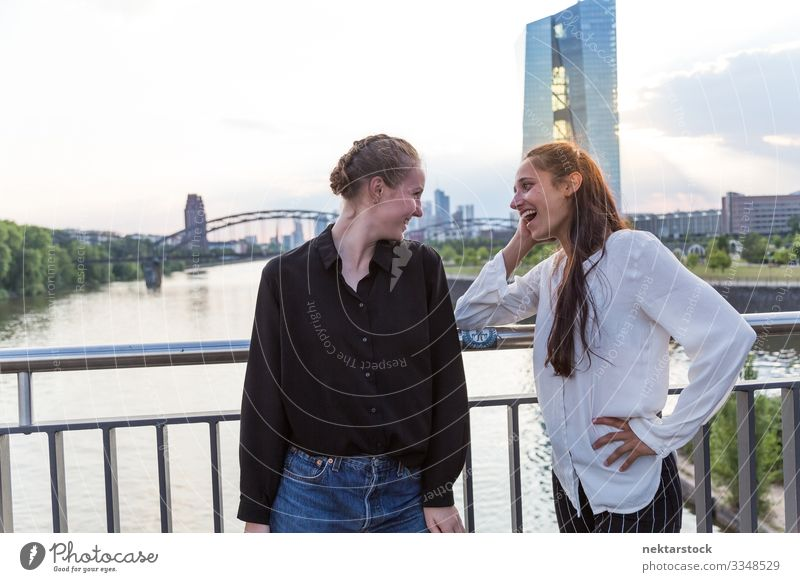 Zwei Frauen mit Blickkontakt auf der Brücke mit Stadthintergrund Erwachsene Freundschaft Jugendliche Skyline Lächeln Liebe Fröhlichkeit Mädchen reales Leben