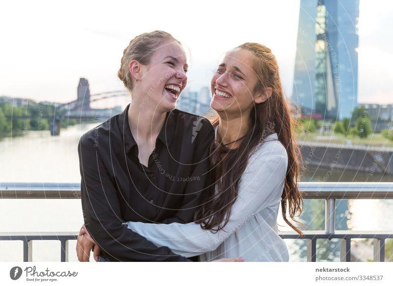 Freundinnen umarmend und lachend auf der City Bridge Freude Glück Frau Erwachsene Freundschaft Jugendliche Jugendkultur Natur Fluss Hochhaus Brücke Gebäude