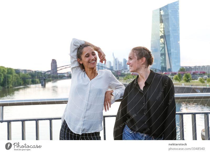 Freundinnen lächeln auf der Stadtbrücke über den Fluss Glück Frau Erwachsene Freundschaft Jugendliche Jugendkultur Natur Hochhaus Brücke Gebäude Lächeln Mädchen