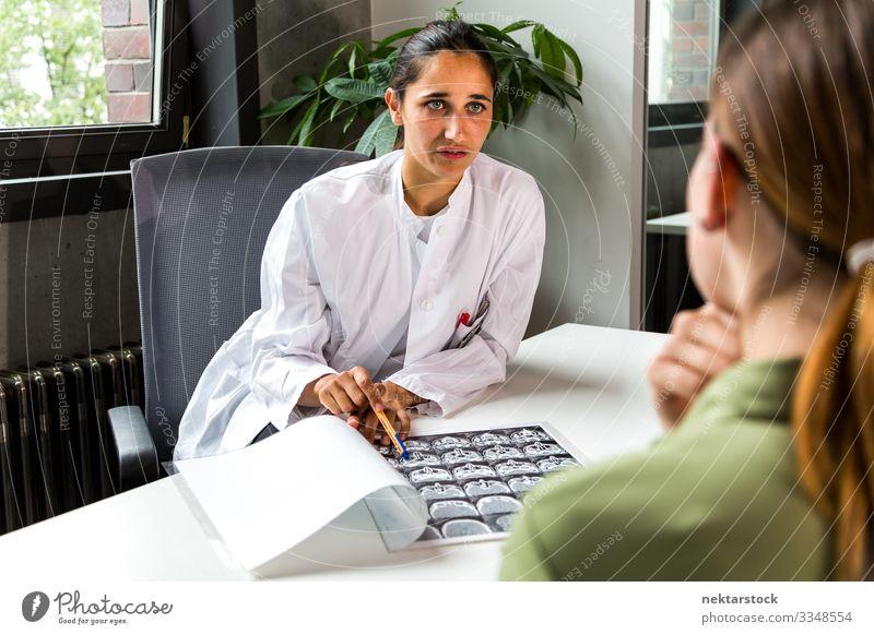 Junge Mediziner zeigen dem Patienten den CT-Scan Gesundheitswesen Schreibtisch Beruf Arzt Büro Karriere sprechen Frau Erwachsene Jugendliche Ehrlichkeit