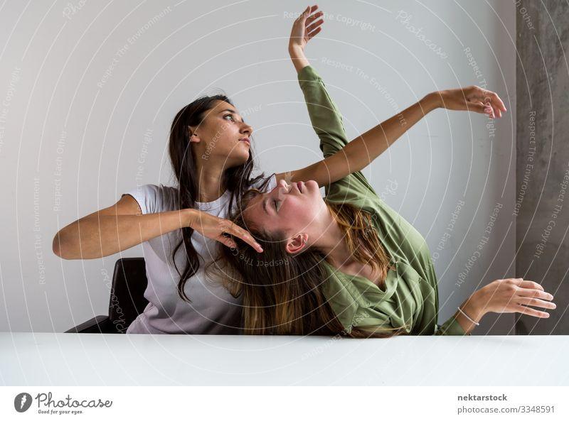 Zwei Frauen posieren künstlerisch im Büro 6 Schreibtisch Tanzen Erwachsene Freundschaft Jugendliche Jugendkultur sitzen Entwurf Arme hochgezogen