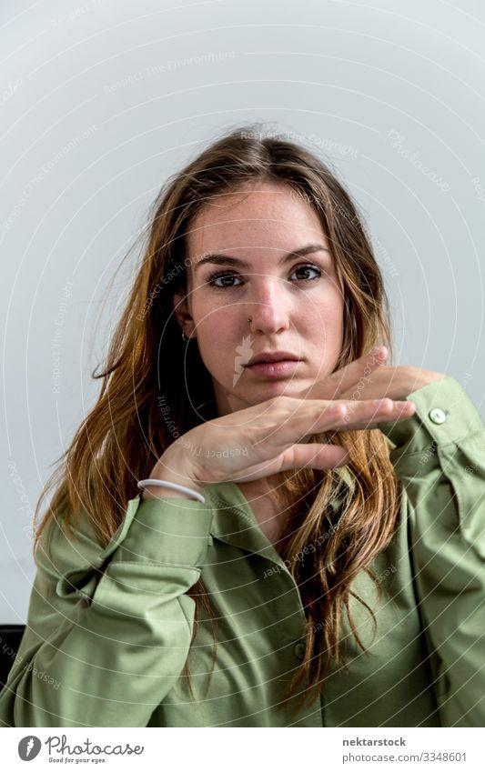Porträt einer jungen Frau, die in die Kamera schaut 2 schön Gesicht Erwachsene Jugendliche Hand Jugendkultur weiß Mädchen Wand Kaukasier