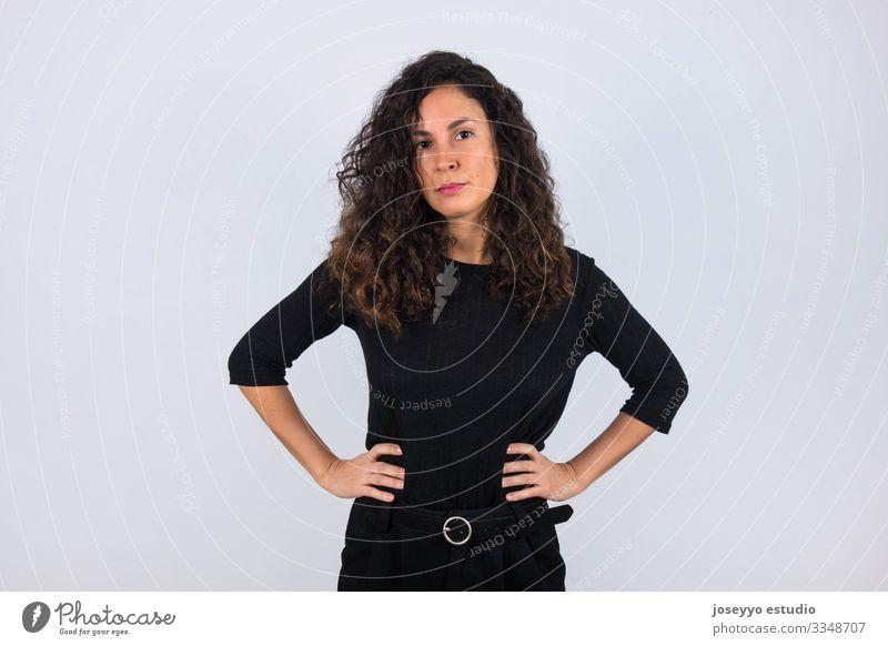 Lockenhaarige brünette Frau in Schwarz mit den Händen in der Taille und Blick in die Kamera. 30-40 Jahre Inserat Einstellung Hintergrund Schönheit braun lässig