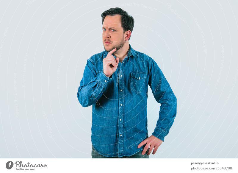 Junger Mann mit Ausdruck von Uneinigkeit und Entschlossenheit. Denim-Hemd und isolierter grauer Hintergrund. 30-40 Jahre Inserat Werbung analytisch Einstellung
