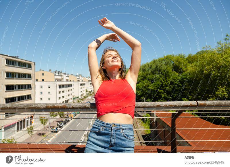 Junge schöne Frau beim Sonnenbaden auf einer Brücke über die Stadt Lifestyle Freude Glück Erholung Freizeit & Hobby Sommer Erwachsene Jugendliche Arme Natur