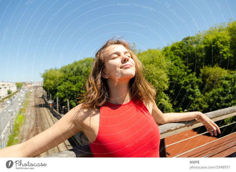 Junge schöne Frau beim Sonnenbaden auf einer Brücke über die Stadt Lifestyle Freude Glück Erholung Freizeit & Hobby Sommer Erwachsene Jugendliche Natur Wind