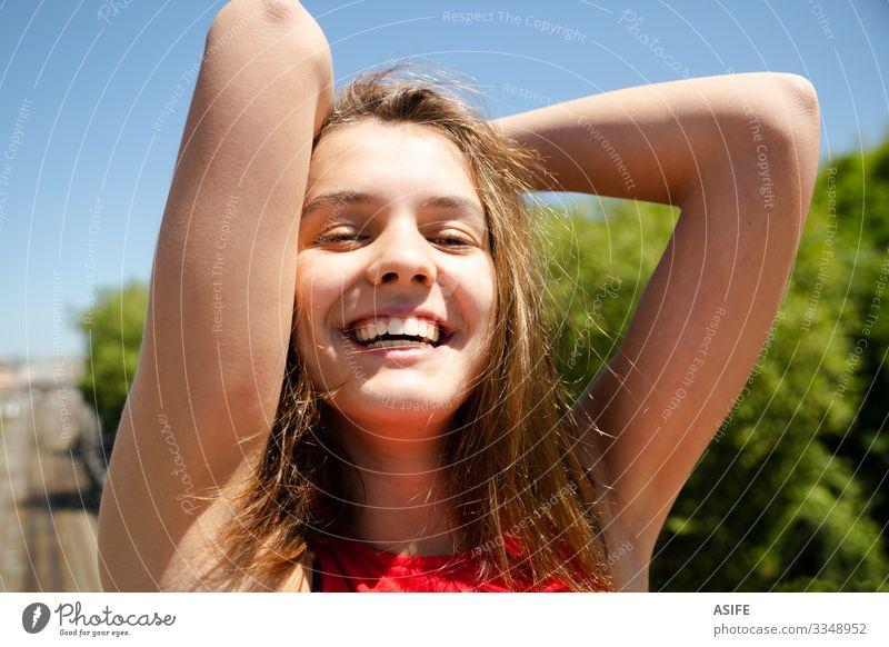 Lachende Jugendliche genießen die Sonne in der Stadt Lifestyle Freude Glück schön Erholung Freizeit & Hobby Sommer Frau Erwachsene Arme Natur Wind Baum Park